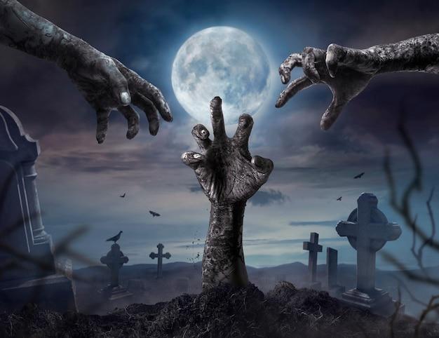 Zombie manos levantándose en la noche oscura de halloween.