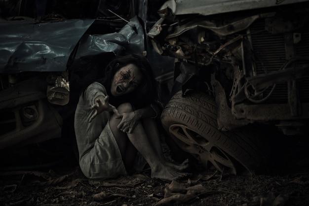 Zombie mujer sentada estirando la mano a la cámara para el festival de halloween