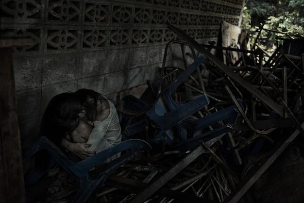 Zombie mujer sentada en la rodilla con muchas sillas de poca luz para el festival de halloween