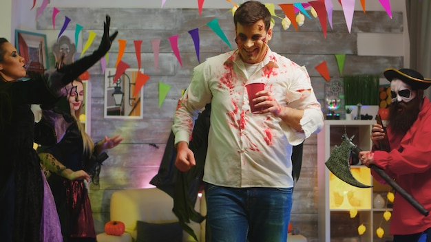 Zombie peligroso borracho celebrando halloween con otros personajes espeluznantes bailando en el fondo.