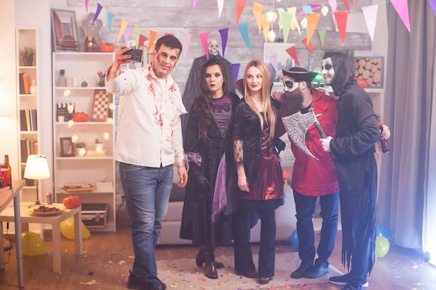 Zombie sangriento tomando un selfie con sus amigos en la fiesta de halloween.