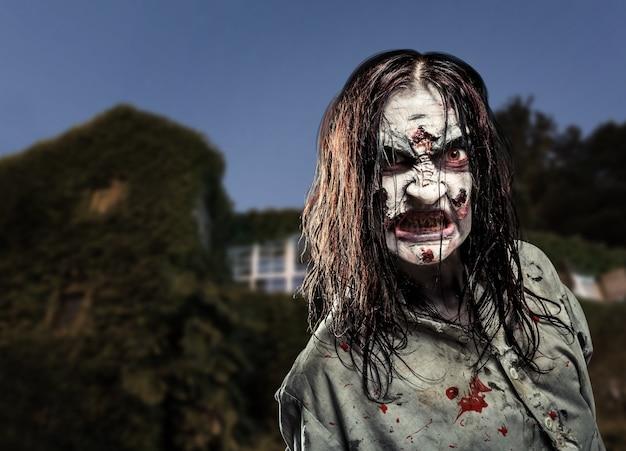 Zombie de terror cerca de la casa abandonada. víspera de todos los santos.