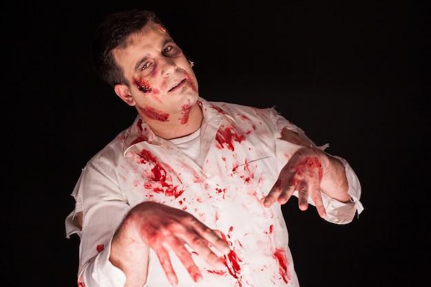 Zombie violento con maquillaje creativo sangriento sobre fondo negro. hombre muerto.