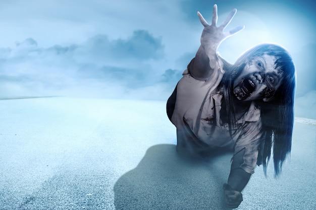 Zombies terroríficos con sangre y heridas en su cuerpo arrastrándose por la carretera de asfalto