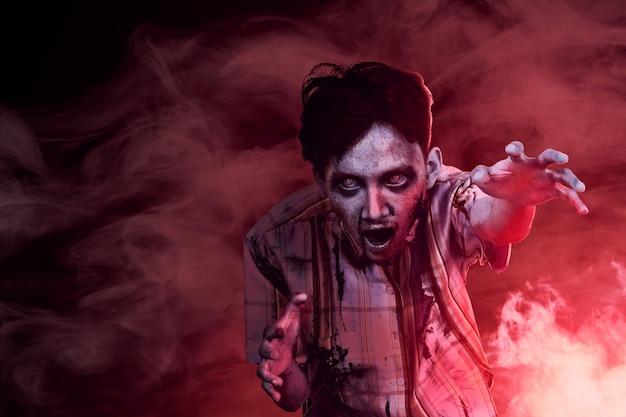Zombies terroríficos con sangre y heridas en su cuerpo caminando en medio de la oscura niebla