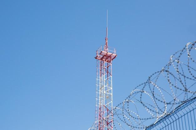 Zona con alambre de púas. zona peligrosa. territorio privado. torre de energia