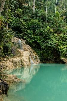 Zona de baño vacía de agua turquesa con la cascada mudal