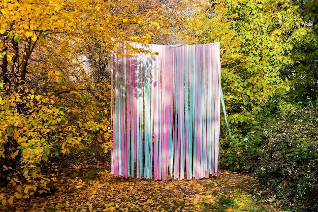 Zona de fotos de otoño festivo en las calles de cintas multicolores, espacio libre para inscripciones. concepto de vacaciones