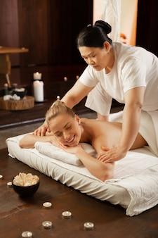 Zona de hombros. mujer asiática de cabello oscuro enfocada que es una maestra de masajes experimentada y trabaja con una clienta