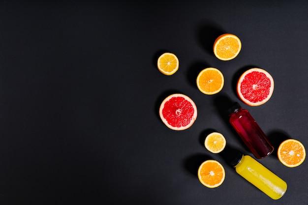 Zumo de cítricos recién exprimido en botellas se encuentra rodeado por mitades de naranja, limón y pomelo en la pared