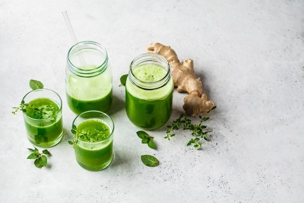 Zumo de desintoxicación verde con jengibre y menta en vasos y tarros.