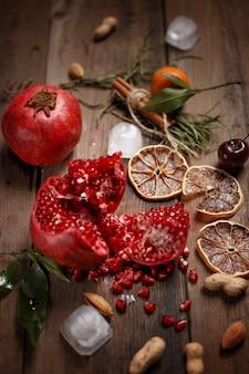 Zumo de granada con granadas y frutos secos sobre una mesa de madera. estilo rústico.
