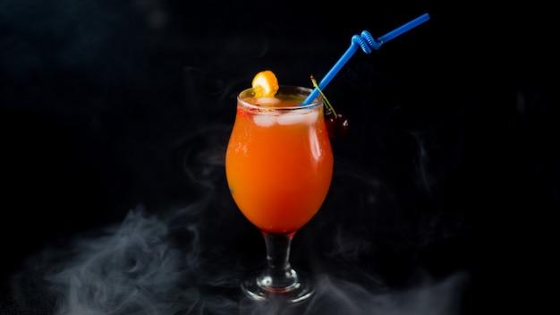 Zumo de naranja con cerezas rojas pipa azul y cubitos de hielo.