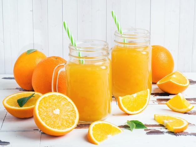Zumo de naranja en frascos de vidrio y naranjas frescas sobre una mesa rústica de madera blanca.
