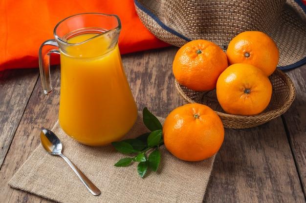 Zumo de naranja fresco en un vaso y naranja fresca