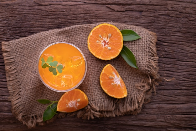 Zumo de naranja frío y naranja en rodajas sobre mesa de madera.