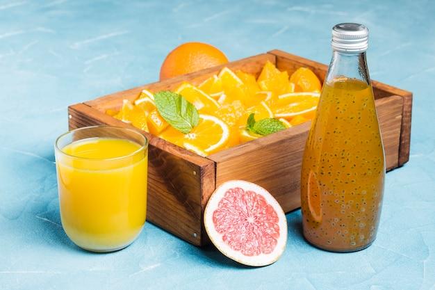 Zumo de naranja y fruta en caja de madera.