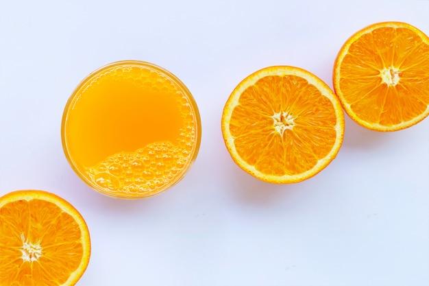 Zumo de naranja con fruta de naranja sobre fondo blanco.