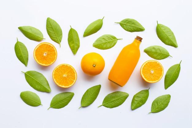 Zumo de naranja con las hojas verdes en el fondo blanco.