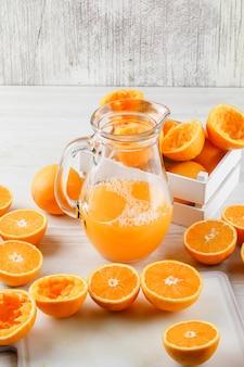 Zumo de naranja en una jarra con naranjas, vista de ángulo alto de tabla de cortar sobre superficie de madera