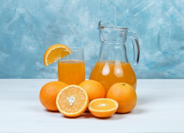 Zumo de naranja con naranjas en jarra y vaso