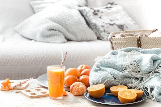 Zumo de naranja orgánico recién cultivado en el interior de la casa, con una manta turquesa y una cesta de frutas.