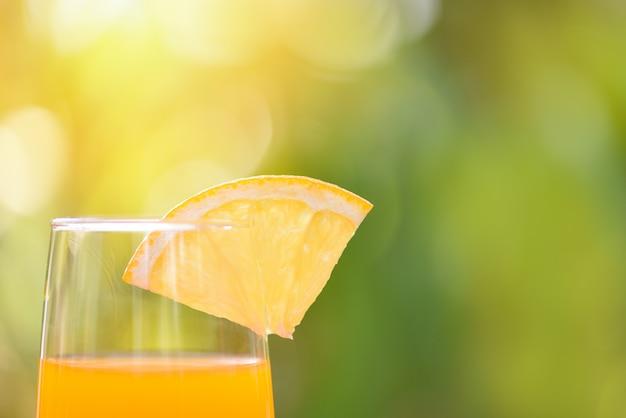 Zumo de naranja con pieza fruta naranja sobre vidrio con naturaleza verde verano