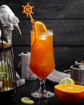 Zumo de naranja con rodaja de naranja y hielo.