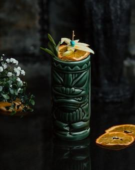 Zumo de naranja con rodajas de fruta en un frasco verde étnico