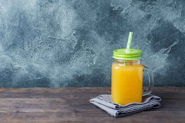 Zumo de naranja en el tarro de cristal en fondo oscuro con el espacio de la copia.