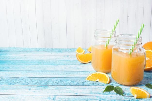 Zumo de naranja en los tarros de cristal y las naranjas frescas en un fondo azul.
