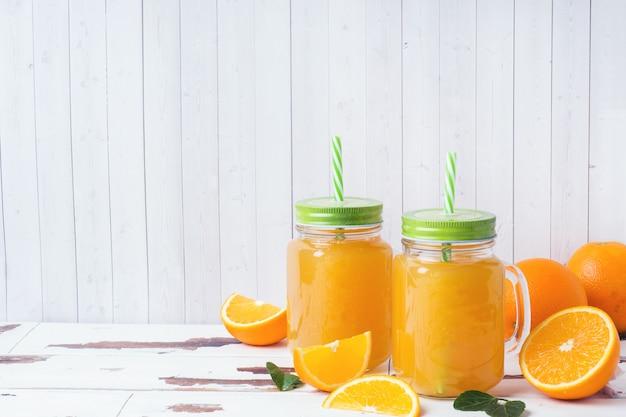 Zumo de naranja en los tarros de cristal y las naranjas frescas en un fondo rústico de madera blanco.
