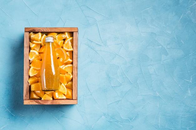 Zumo de naranja de topview en el espacio azul de la copia del fondo