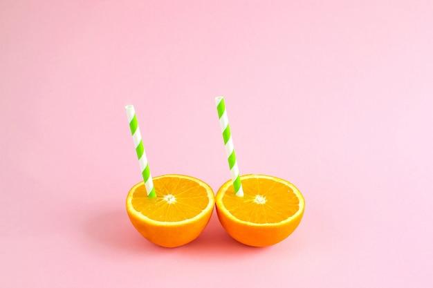 Zumo de naranja con túbulo. naranja cortada por la mitad sobre fondo de color rosa pastel.
