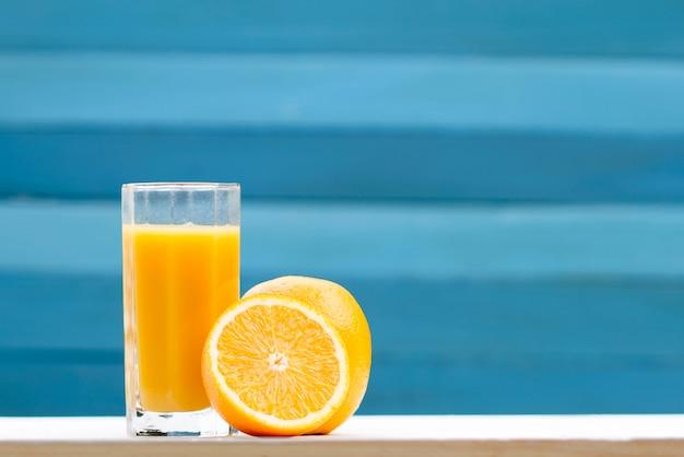 Zumo de naranja en vaso y fruta.
