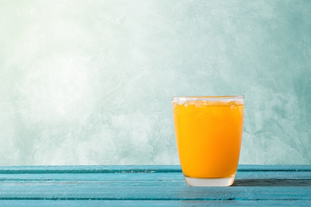 Zumo de naranja en vidrio con hielo en concepto de madera del tiempo de verano del azul de océano.