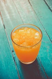 Zumo de naranja de la visión superior en vidrio con hielo en concepto de madera del tiempo de verano del azul de océano.