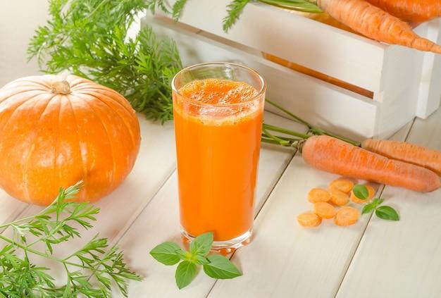 Zumo de zanahoria y calabaza recién exprimido en un vaso sobre una mesa de madera blanca con zanahorias frescas