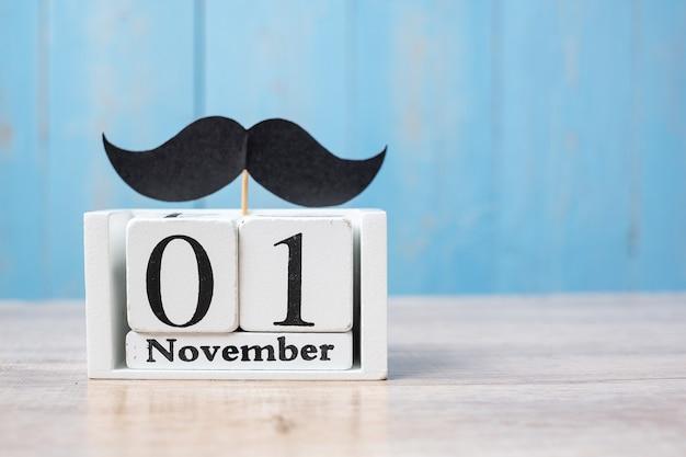 1 novembre calendario e baffi sul tavolo di legno. padre, giornata internazionale degli uomini, consapevolezza del cancro alla prostata