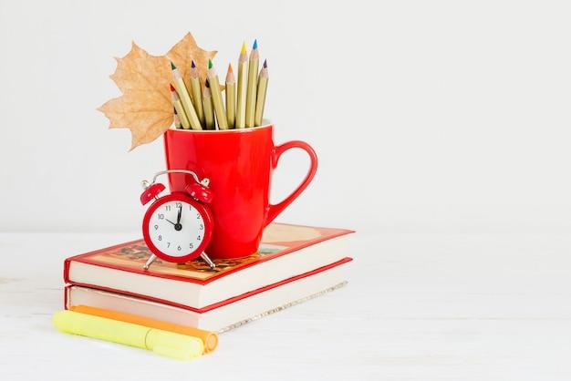 1 ° settembre concept. sveglia rossa, tazza, matite colorate, libri e foglia d'acero. torna al concetto di scuola