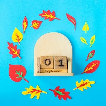 1 settembre su un calendario di legno su uno sfondo blu tra le foglie di autunno di carta