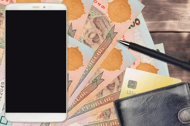 100 banconote hryvnias ucraine e smartphone con borsa e carta di credito.