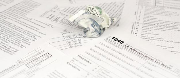 1040 modulo per la dichiarazione dei redditi individuali e una banconota da cento dollari accartocciata