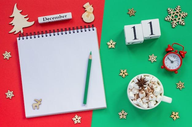 11 dicembre, tazza di cacao e marshmallow e blocco note aperto vuoto con la matita