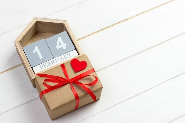 14 febbraio. calendario in legno con cuore rosso e scatola regalo in cima carta di san valentino.