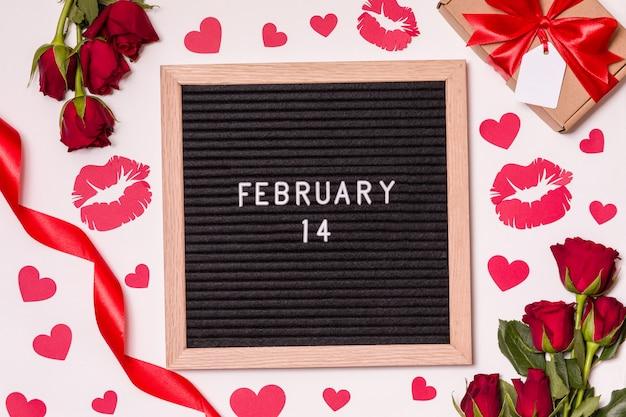 14 febbraio sulla scheda della lettera con sfondo san valentino - rose rosse, baci e cuori.