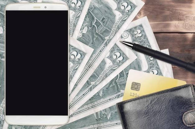 2 banconote in dollari usa e smartphone con borsa e carta di credito. pagamenti elettronici o concetto di commercio elettronico.
