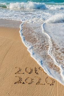 2019 2020 scritto nella sabbia con un'onda che cancella il 2019