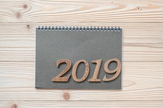 2019 happy new year con il taccuino sulla tavola di legno