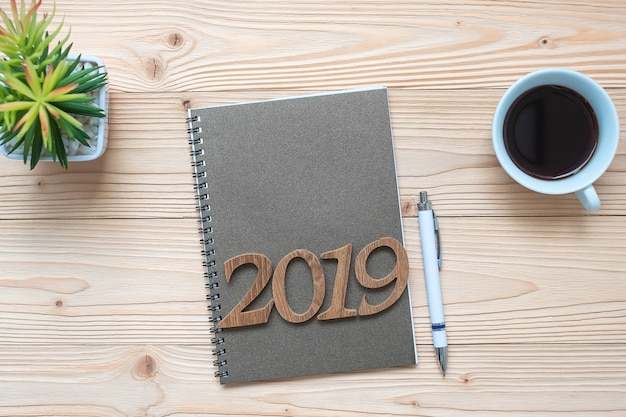 2019 happy new year con notebook, tazza di caffè nero, penna e bicchieri